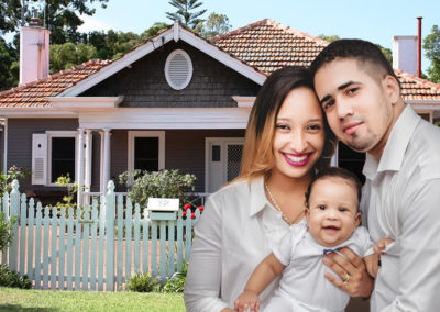 Photo of Latino couple with baby smiling in front of home they've bought. For article on mortgages for BorrowingBetter.COm.