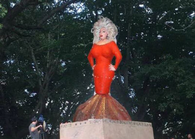 Photo of Divine in a red fishtail dress standing on a pedestal in a park.